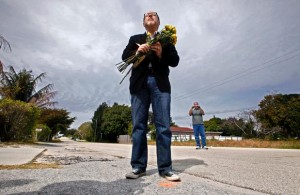 Rev. Patrick J. Mahoney, director of the Christian Defense Coalition, says a prayer before laying flowers on SW 2nd Avenue in Boynton Beach where two street preachers were shot and killed in January